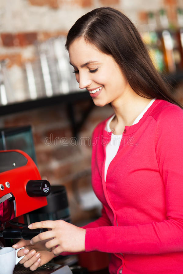 Female barista by coffee maker royalty free stock images