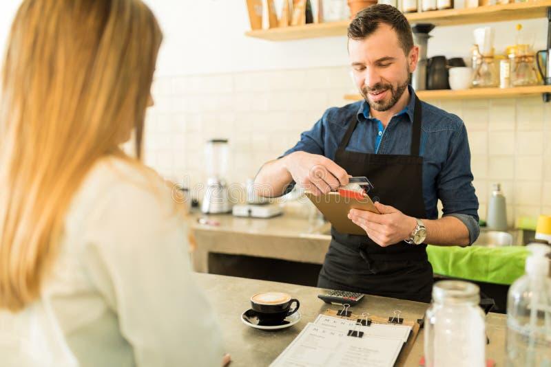 Barista swiping kredytową kartę w sklep z kawą obraz royalty free