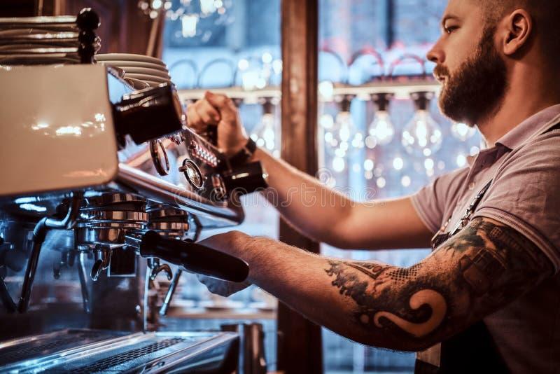 Barista tatuado con el funcionamiento elegante de la barba y del peinado en una máquina del café en una cafetería o un restaurant imagen de archivo libre de regalías