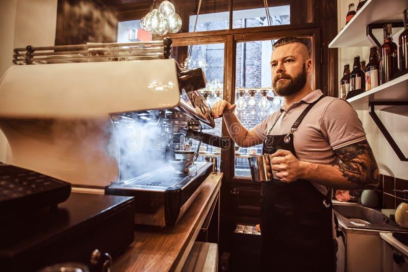 Barista tatuado con el funcionamiento elegante de la barba y del peinado en una máquina del café en una cafetería o un restaurant imágenes de archivo libres de regalías