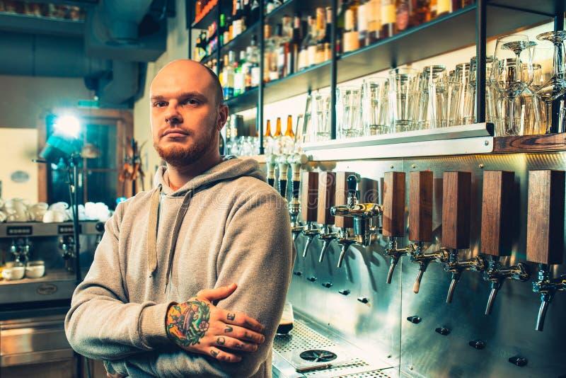 Barista in un pub vicino ai rubinetti della birra fotografie stock libere da diritti