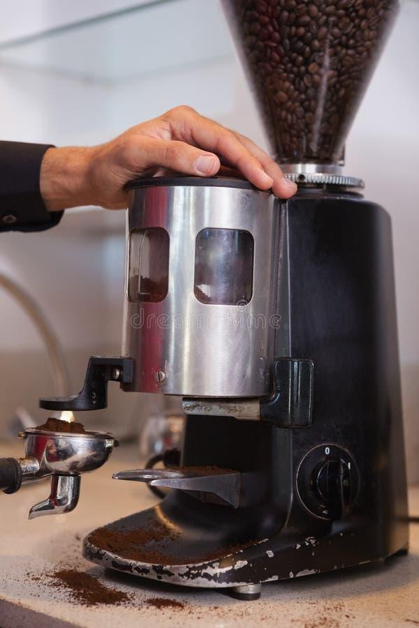 Barista unter Verwendung der Kaffeemühle, zum von Bohnen zu reiben lizenzfreie stockfotos