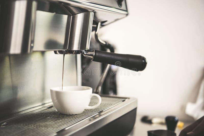 Barista usando la extracción de la cafetera para el café express tiró en café imágenes de archivo libres de regalías