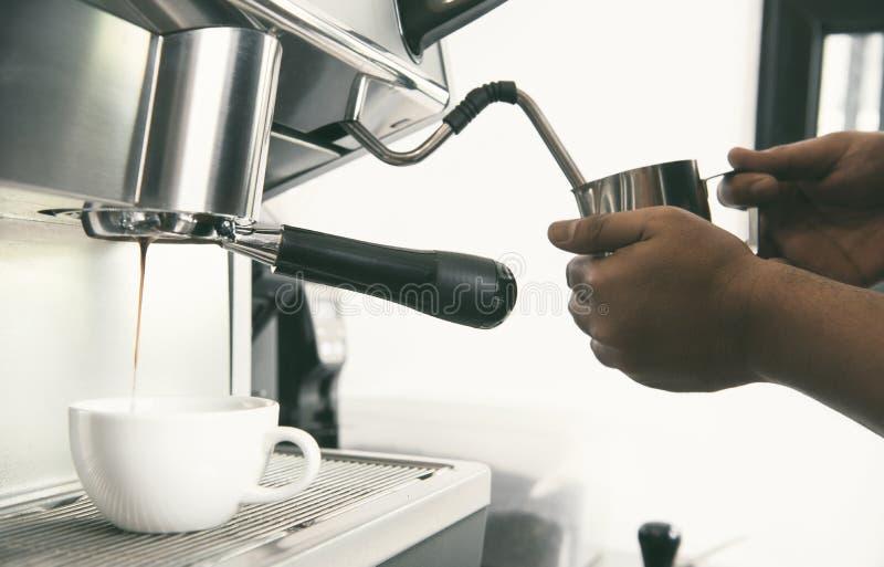 Barista usando la extracción de la cafetera para el tiro y el vapor del café express imágenes de archivo libres de regalías