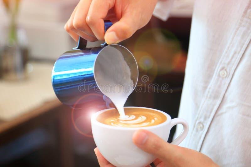 Barista usando la jarra para verter la leche espumejeada para ahuecar de modelo del tulipán del latte del café en el top imagen de archivo
