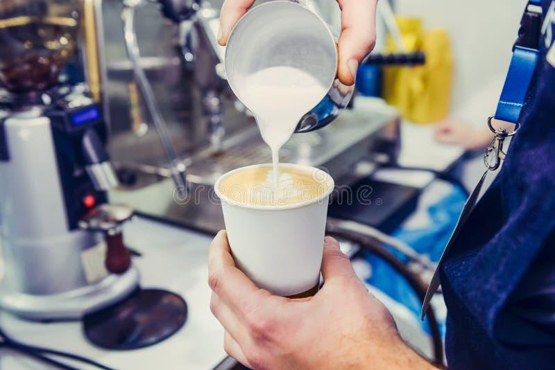Barista usando la máquina del café que prepara el café fresco y que vierte la leche al café del café express hace arte del latte  foto de archivo
