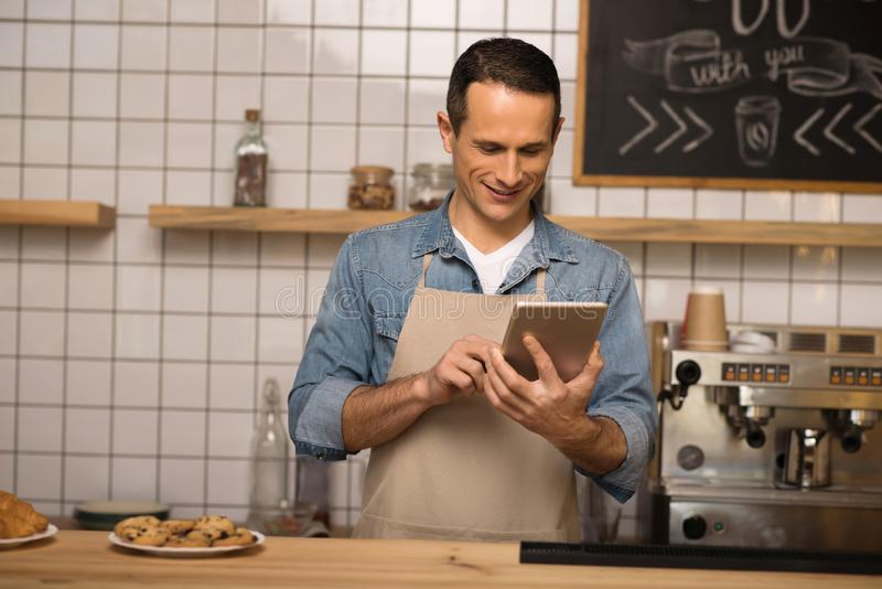 Barista using digital tablet. Portrait of smiling barista using digital tablet in cafe royalty free stock photography