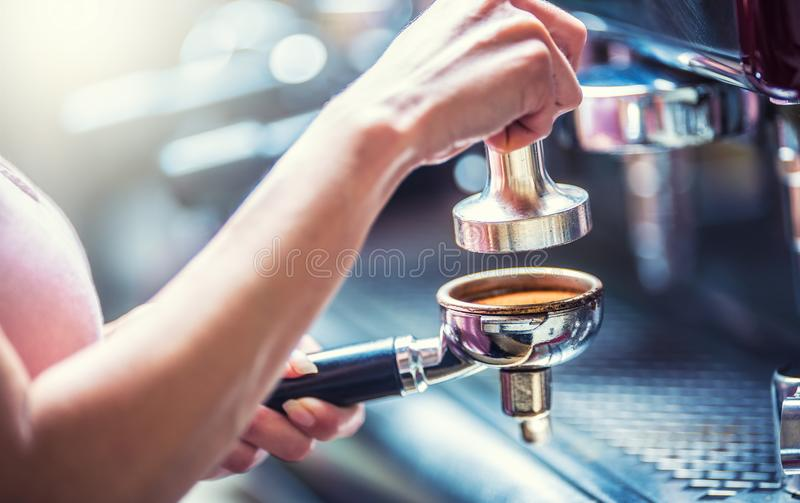 Barista woman making an espresso coffee. Barista woman making an espresso coffee with portafilter and coffee tamper royalty free stock images