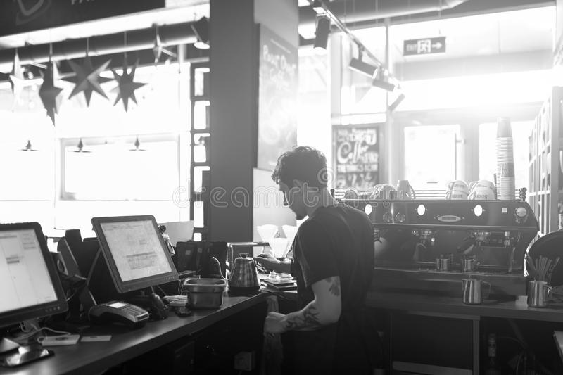 Barista at work in a coffee shop. Preparation service concept. Black and white photo stock image
