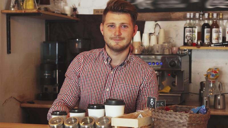 Barista clears the bar counter. The barista is working in the cafe. He clears the bar counter. He arranges cups. He seems very satisfied and happy royalty free stock photography