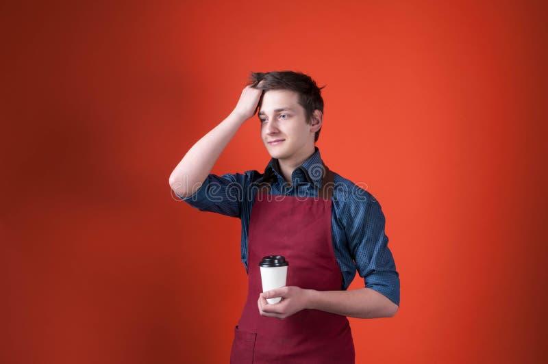Barista z ciemnym włosy patrzeje daleko od w Burgundy fartuchu, trzyma papierową filiżankę z kawą i koryguje fryzurę na pomarańcz zdjęcia stock