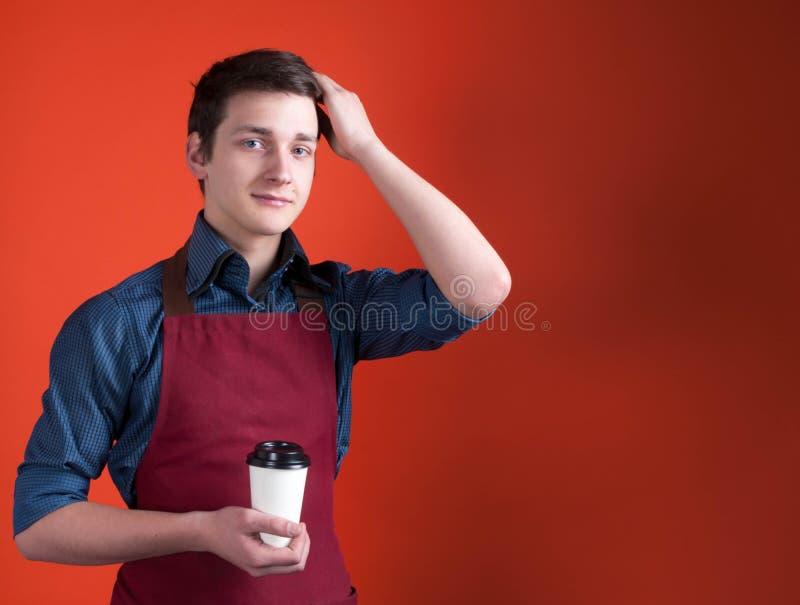 barista z ciemnym włosy patrzeje kamerę w Burgundy fartuchu, trzyma papierową filiżankę z kawą i koryguje fryzurę na pomarańcze p obrazy stock