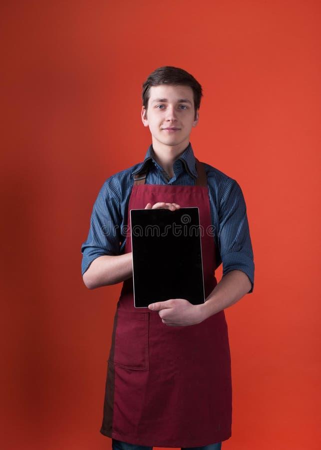 Barista z ciemnym włosy w błękitnej koszula i Burgundy fartuchu trzyma cyfrową pastylkę z pustym ekranem, pokazuje i patrzeje kam zdjęcie stock