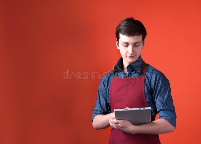 Barista z ciemnym włosy w Burgundy fartucha mieniu i patrzeć cyfrową pastylkę na pomarańczowym tle obrazy stock