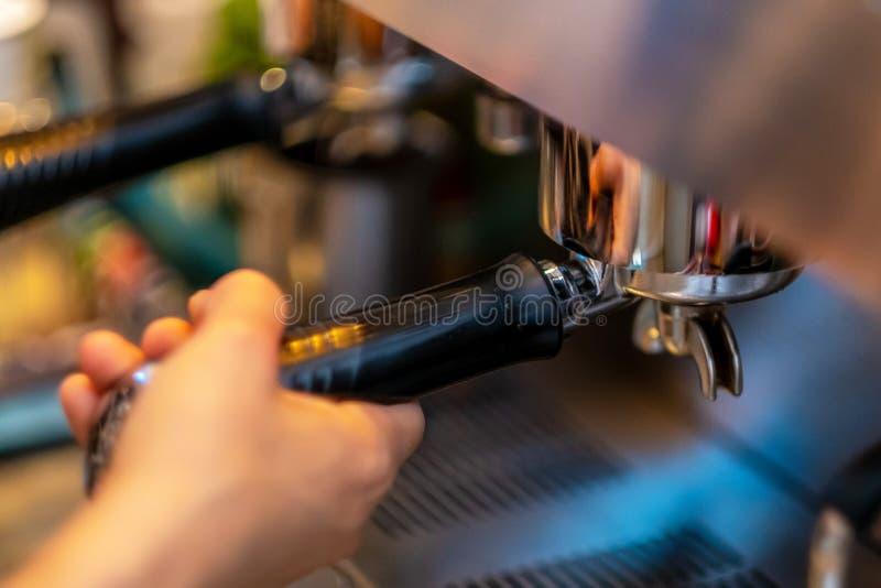 Baristahanden die koffie van de machine maken stock afbeeldingen