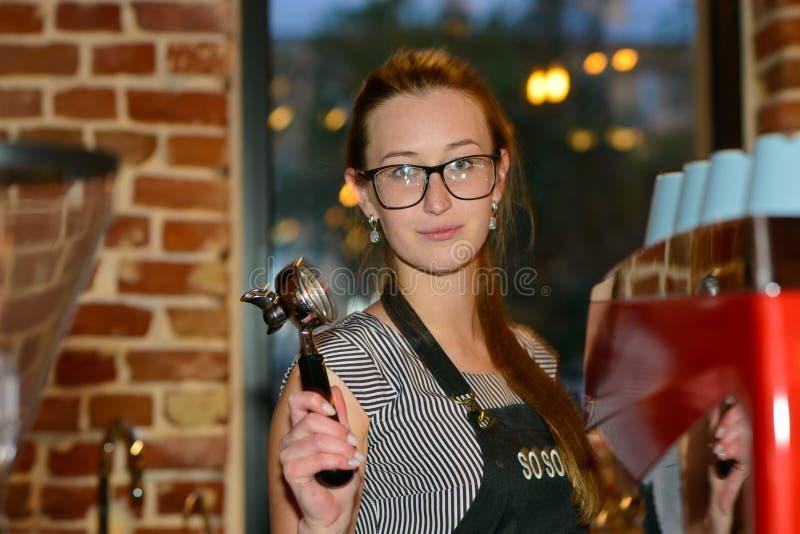 Baristameisje met ontvanger in hand achter de bar in de koffie royalty-vrije stock foto