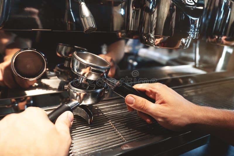 Baristamens die twee koffiehouders dicht tegenhouden boven andere op de achtergrond van de koffiemachine stock afbeelding