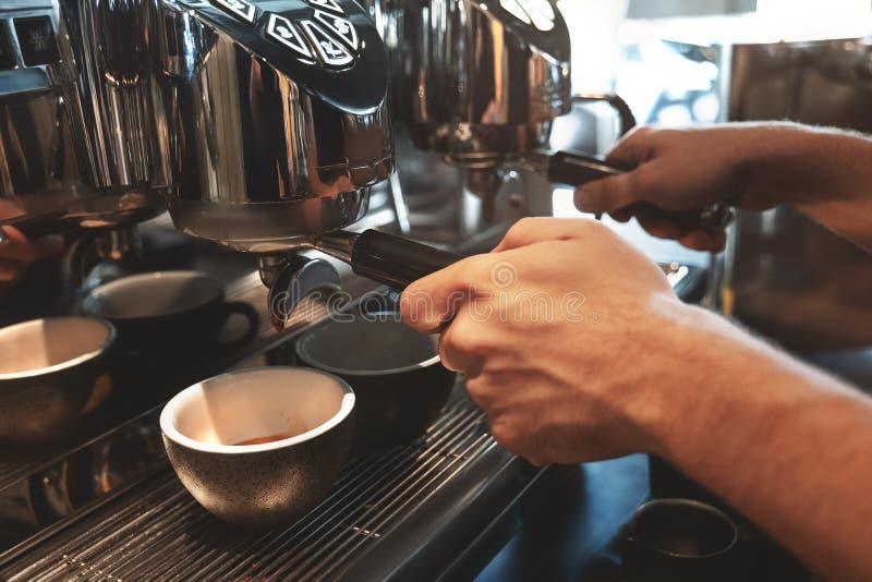 Baristamens die twee koppen van koffie maken tegelijkertijd het gebruiken van professionele koffiemachine in koffie drinken stock afbeeldingen