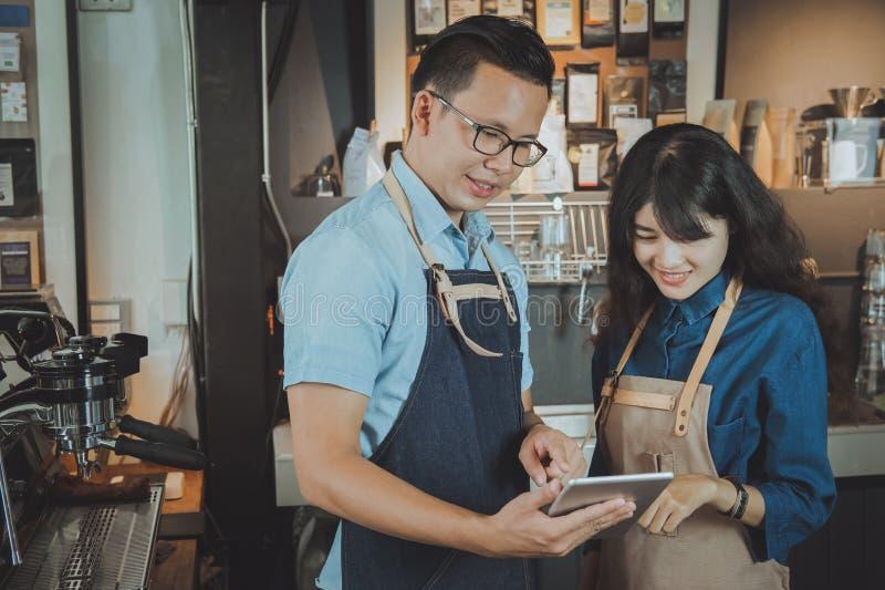 Baristas asiáticos que toman una orden por la tableta digital Restauran del café fotos de archivo libres de regalías