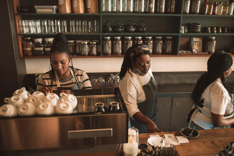 Baristas and waitresses working behind the counter of a cafe stock photos