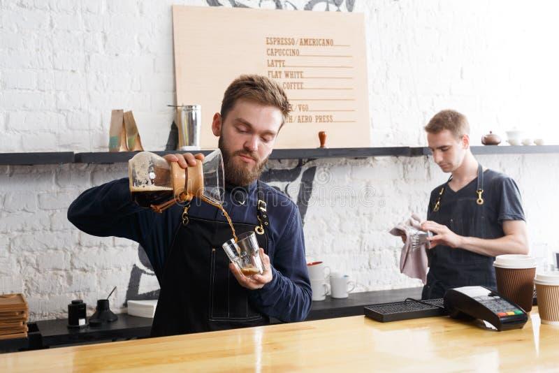Baristi maschii che fanno caffè fresco all'interno del caffè fotografia stock libera da diritti