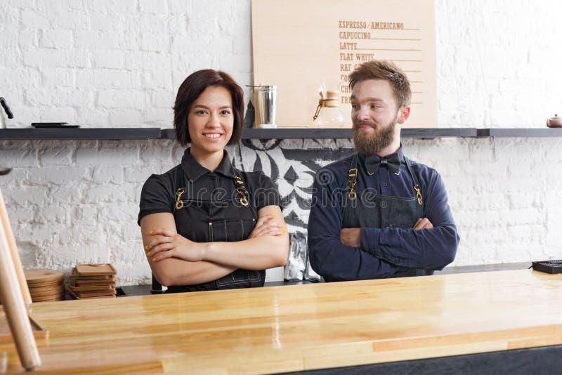 Baristi maschii e femminili in caffè uniforme all'interno del caffè immagine stock