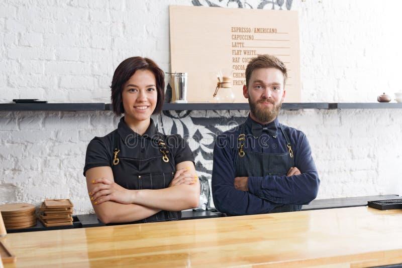Baristi maschii e femminili in caffè uniforme all'interno del caffè fotografia stock
