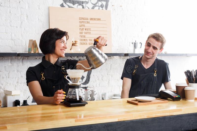 Baristi maschii e femminili che fanno caffè fresco all'interno del caffè immagini stock