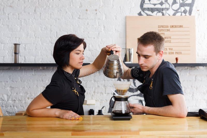 Baristi maschii e femminili che fanno caffè fresco all'interno del caffè immagine stock libera da diritti