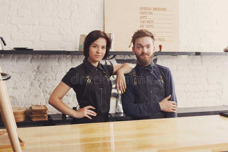 Baristi maschii e femminili in uniforme del caffè fotografia stock libera da diritti