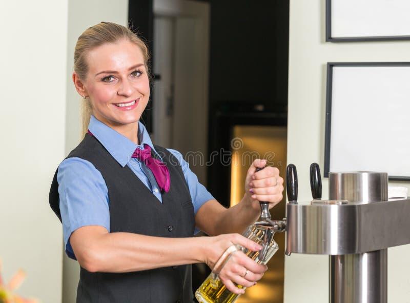 Barkeeper i fyllnads- exponeringsglas för stång eller för bar med öl arkivfoto