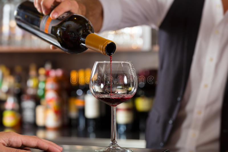 Red wine pouring in glass at bar. Barkeeper pouring red wine in glass on bar in restaurant or hotel royalty free stock images