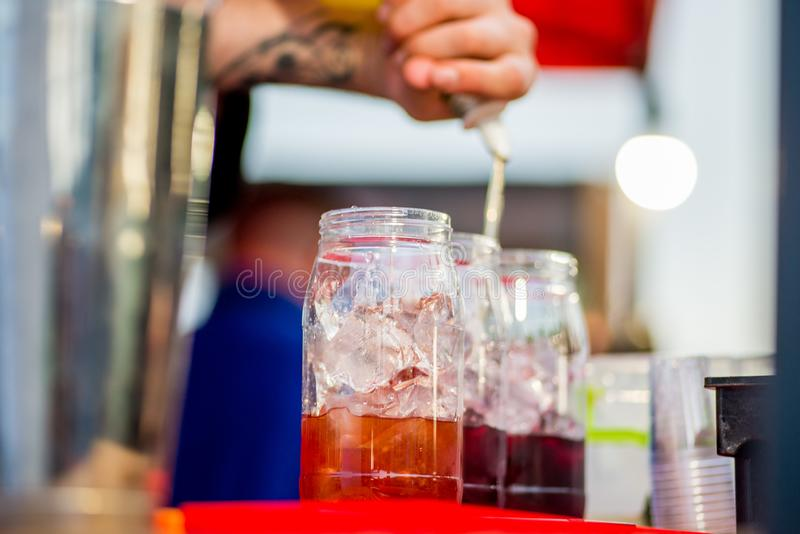 Barkeeper preparing a cocktail. In a plastic glass outdoors. catering stock photography
