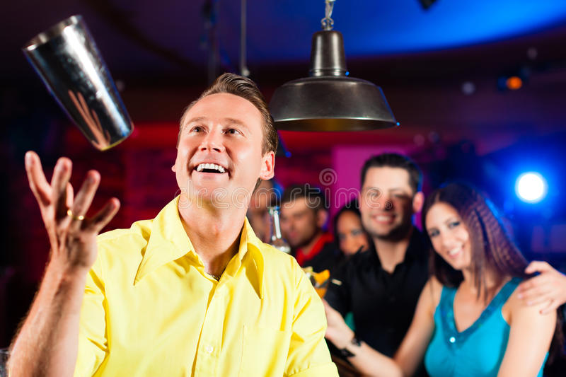 Barkeeper in a pub is mixing cocktails or drinks royalty free stock image