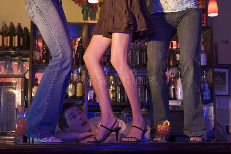 Barkellner, der bei drei jungen Frauen tanzen auf Stab den Mund aufsperrt stockbild