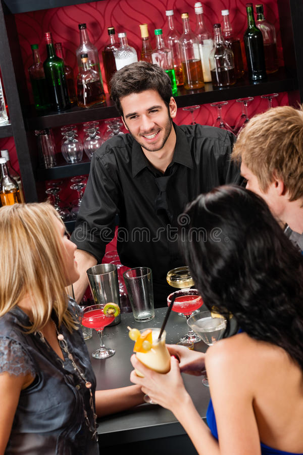 Barkellner, der mit den Freunden trinken am Stab plaudert stockfotos