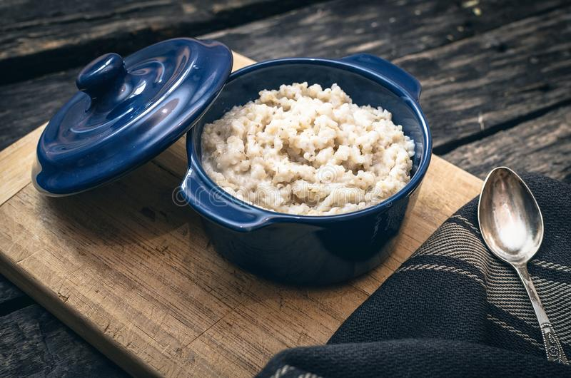 Barley porridge. Barley porridge in the blue ceramic pot on dark aged wooden background. Healthy breakfast royalty free stock image