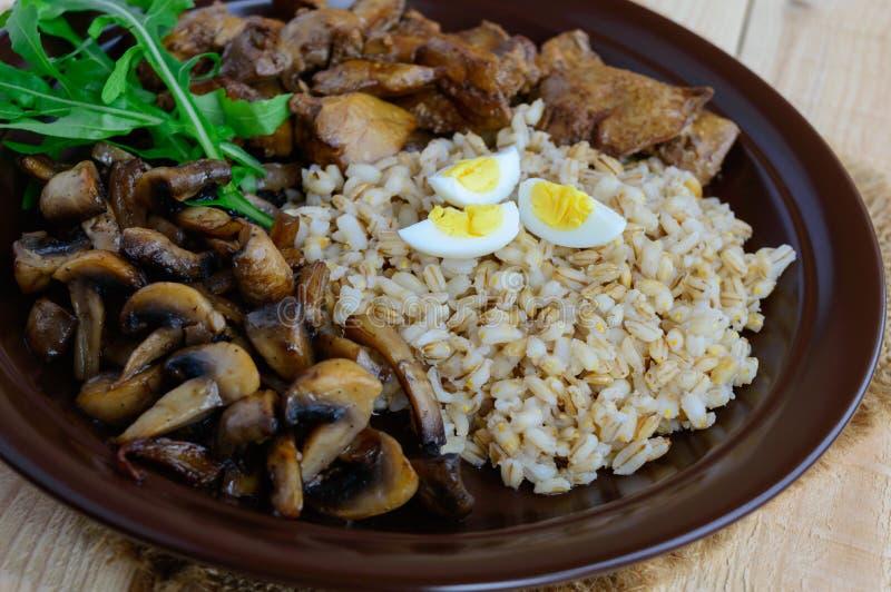 Barley porridge, fried mushrooms and duck liver, boiled quail eggs, tomatoes, arugula - healthy food.  royalty free stock photo
