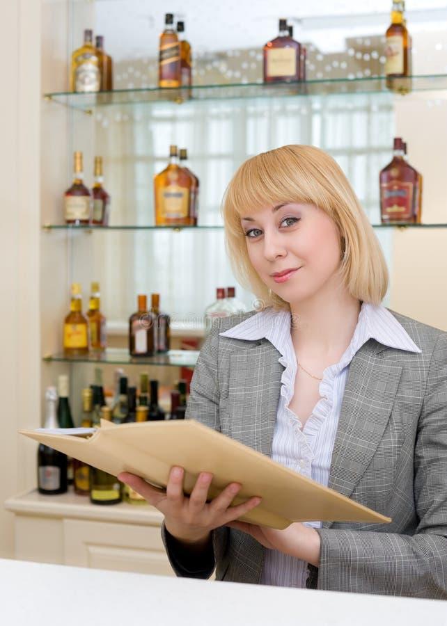 Barmaid à un bar avec la liste de vin image stock