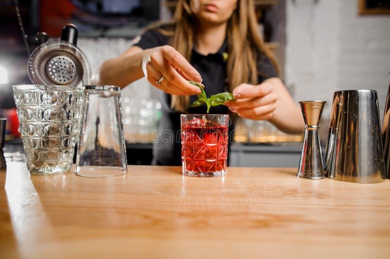 Barmaid blonde ajoutant aux feuilles en bon état de cocktail image stock