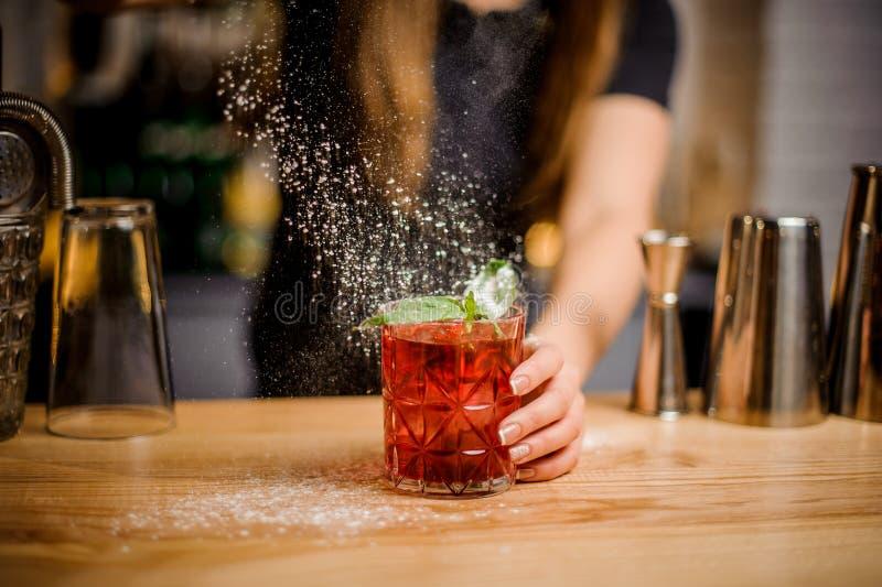 Barmaid Blondy заканчивает подготовку коктеиля путем добавлять горькое напудренного сахара стоковое фото