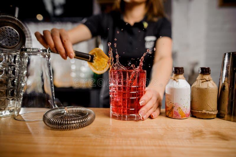 Barmaid d'exploit ajoutant à la tranche en verre de cocktail de citron utilisant des pinces photo stock