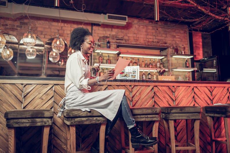 Barmaid enchantante lisant complètement le menu tout en se reposant à la chaise de barre image libre de droits