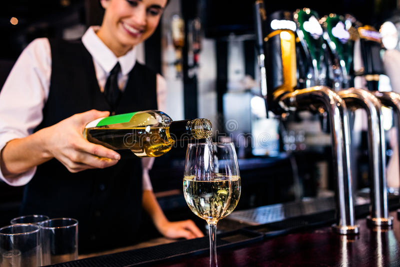 Barmaid servant un verre de vin photo stock