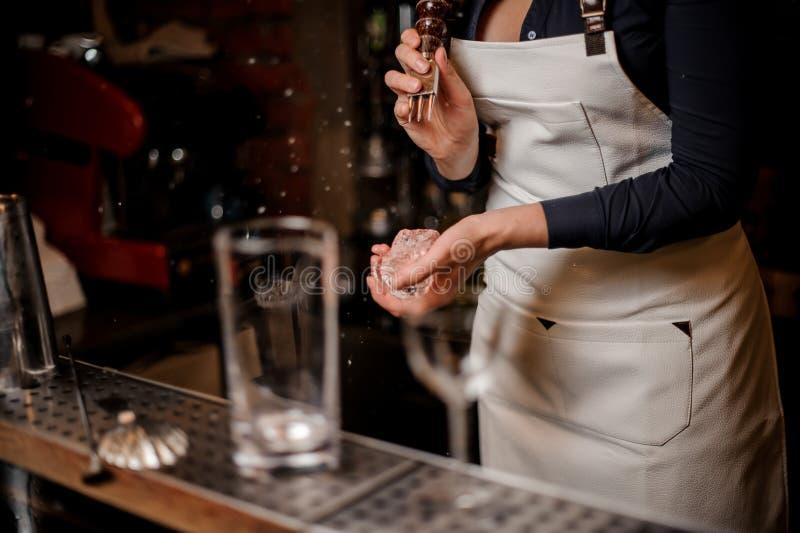 Barmaid sexy écrasant un morceau de glace pour faire le cocktail photographie stock