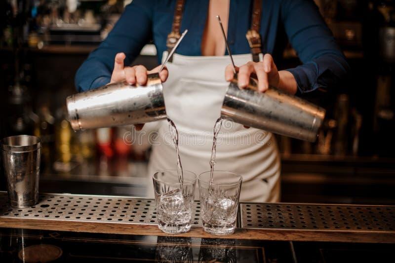 Barmaid versant le cocktail frais d'été des dispositifs trembleurs dans des verres photographie stock libre de droits