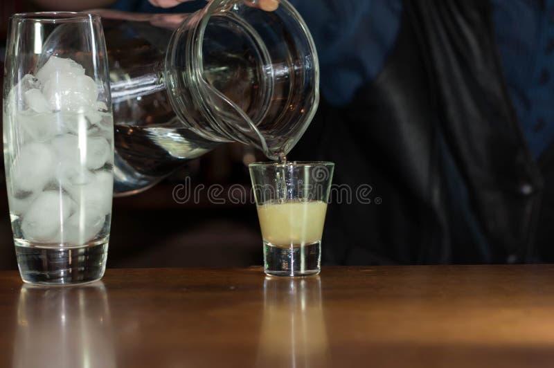 Barman à la soude se renversante de compteur de la cruche dans le verre avec du jus photos stock