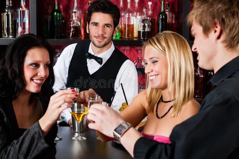 Barman achter tegenvrienden die bij staaf drinken royalty-vrije stock foto