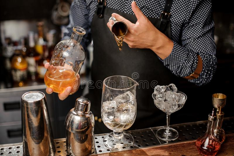 Barman adding a portion of syrup into the large cocktail glass. With ice cubes on the bar counter stock photo