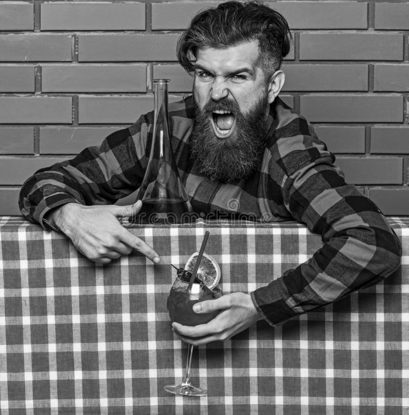 Barman advice concept. Barman with beard on shouting face holds cocktail. Bartender recommends to try beverage. Man in. Checkered shirt near bottle, brick wall royalty free stock images